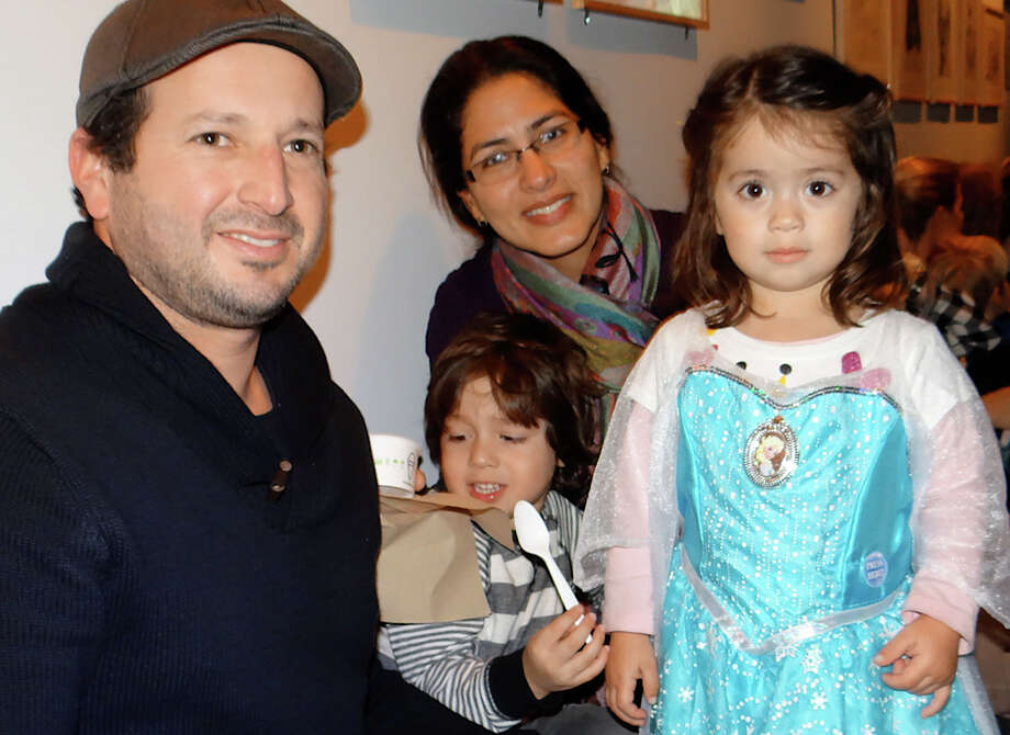 "Pedro and Ana Quintana and children Mauricio, 4, and Victoria, 2, dressed as Elsa, at the ""Frozen"" sing-a-long Sunday at the Westport Library. Photo: Mike Lauterborn / Westport News"