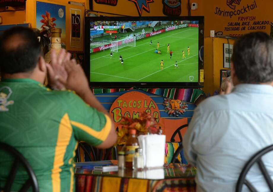 From left, Samuel Gallego and Carlos Sunea cheer at Tacos La Bamba in Beaumont while watching Mexico score against Cameroon in the World Cup on Friday. Photo taken Friday, June 13, 2014 Guiseppe Barranco/@spotnewsshooter