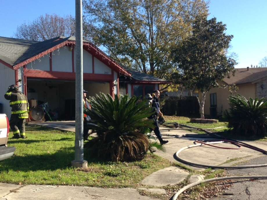 San Antonio fire department crews are battling a house fire on the West Side. The fire began around 9:30 a.m. on December 29, 2014, at a home in the 2100 block of Dove Creek. Photo: Mark D. Wilson/San Antonio Express-News