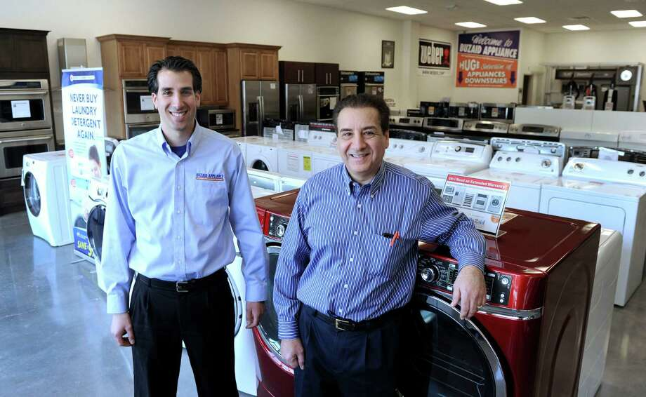 Norman Buzaid Sr., center, owner of Buzaid's Appliances, and his son, also named  Norman, are photographed in the showroom of their new store location at 227 Federal Rd. in Brookfield, Conn., Monday, Dec. 29, 2014. Photo: Carol Kaliff / The News-Times