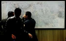 Indonesian officers inspect a map Sunday during the search for the missing AirAsia jet.