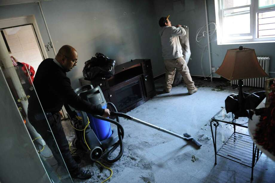 Edwin Vega, left, of Service Management Group, and Gary Ocuma help clean up the inside of an apartment after a fire at the Housing Authority of Greenwich's Wilbur Peck Court apartments in Greenwich, Conn. Monday, Dec. 29, 2014.  A Christmas tree caught on fire before 8 a.m. Monday morning causing fire and smoke damage to the apartment and water damage to the apartment below.  American Red Cross Disaster Relief was called to the scene and will provide emergency relocation for the two families along with loss assistance and comfort kits for the 4- and 9-year-old children. Photo: Tyler Sizemore / Greenwich Time