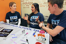 Johnson High School students (right) Brittany Muller and Tyler Otten team up with parent advisor Melinda Cox at Duncan Donuts on TPC Parkway to inform customers of the upcoming new laws concerning texting and driving and also to warn against the dangers of using hand held devices while driving on December 27, 2014.