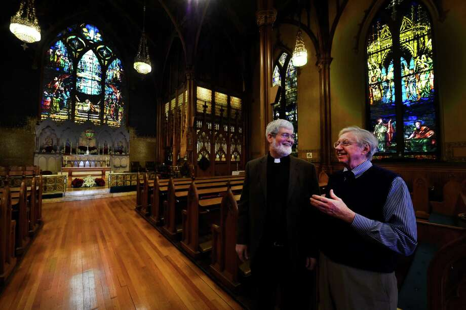 The Rev. Michael Gorchov, rector of St. Paul's Episcopal Church, left, speaks with church historian Ned Pratt as the church opened up its fund raising effort to make repairs to the historic site during a press conference Monday morning Dec. 29, 2014 in Troy, N.Y. The church?s interior was designed by the Louis Comfort Tiffany Co. in the 1890s. (Skip Dickstein/Times Union) Photo: SKIP DICKSTEIN / 00030015A