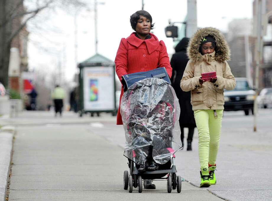 Sakina Mitchell and her two children, Tamani, in the stroller, 2, and Tiani Mitchell, 9, make their way along Washington Ave. on Monday, Dec. 29, 2014 in Albany, N.Y.  The family is visiting from New York City.  (Paul Buckowski / Times Union) Photo: Paul Buckowski