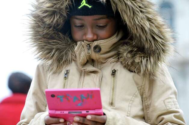 Tiani Mitchell, 9, plays a video game as she walks along Washington Ave. on Monday, Dec. 29, 2014 in Albany, N.Y.  Mitchell and family are visiting from New York City.  (Paul Buckowski / Times Union) Photo: Paul Buckowski
