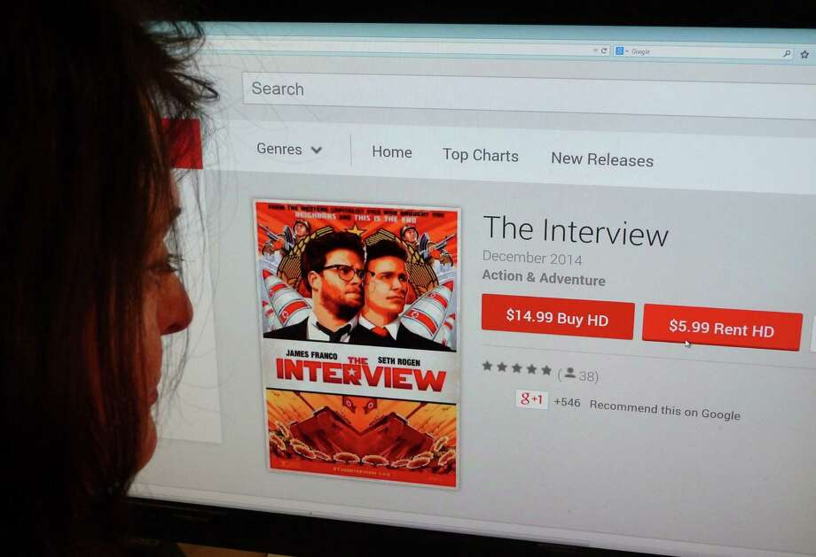 "In this photo illustration, a woman looks at the Google Play purchase page for the Sony film ""The Interview"" in Washington, D.C. Photo: -- / AFP/Getty Images / AFP"