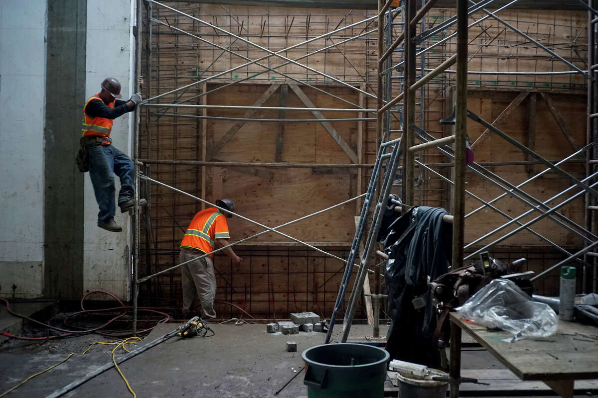 Workers make their way down from the scaffolding in an old racquetball court on Monday, Dec. 22, 2014 in Sunnyvale, Calif. The new building will produce as much energy as it consumes.