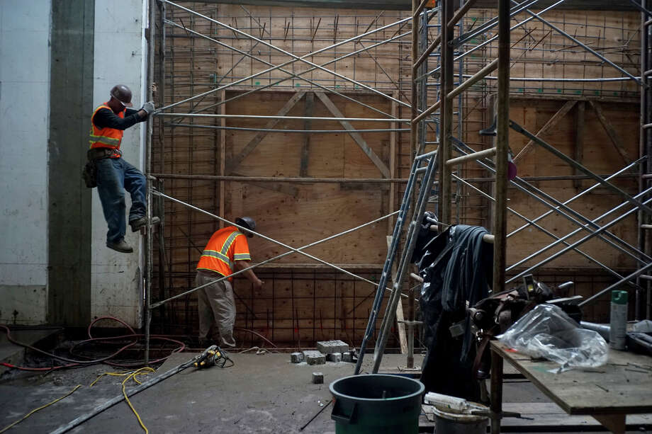 Workers make their way down from the scaffolding in an old racquetball court on Monday, Dec. 22, 2014 in Sunnyvale, Calif. The new building will produce as much energy as it consumes. Photo: James Tensuan / Special To The Chronicle / ONLINE_YES