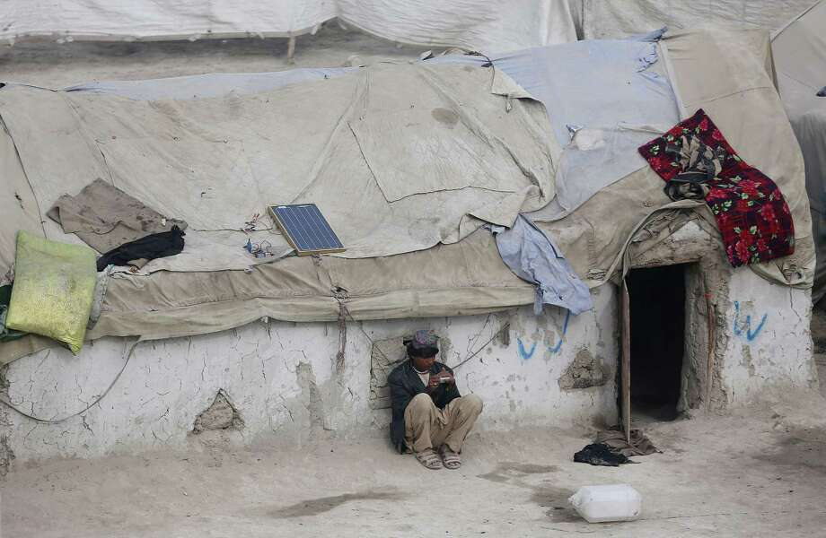 An internally displaced young Afghan man looks at his mobile phone at a makeshift camp in the capital, Kabul. Photo: Massoud Hossaini / Associated Press / AP
