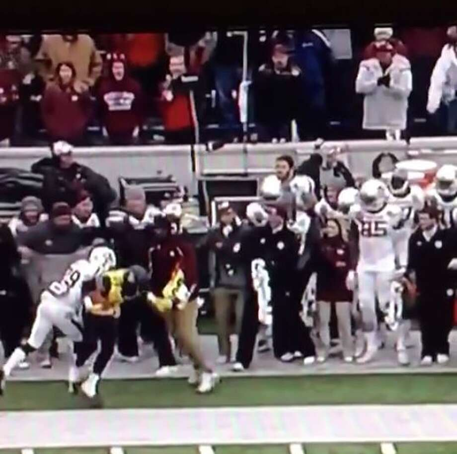 Mike Richardson, former Aggies linebacker and current student assistant to the team, struck at least two West Virginia players during the Liberty Bowl Monday.  Two videos posted to Vine show Richardson — identified on Twitter by Brent Zwerneman, Aggies reporter for the Houston Chronicle — smacking one player over the head and striking another with his shoulder as they cross the sidelines. Photo: Fechter, Joshua I, Screenshot Via Vine