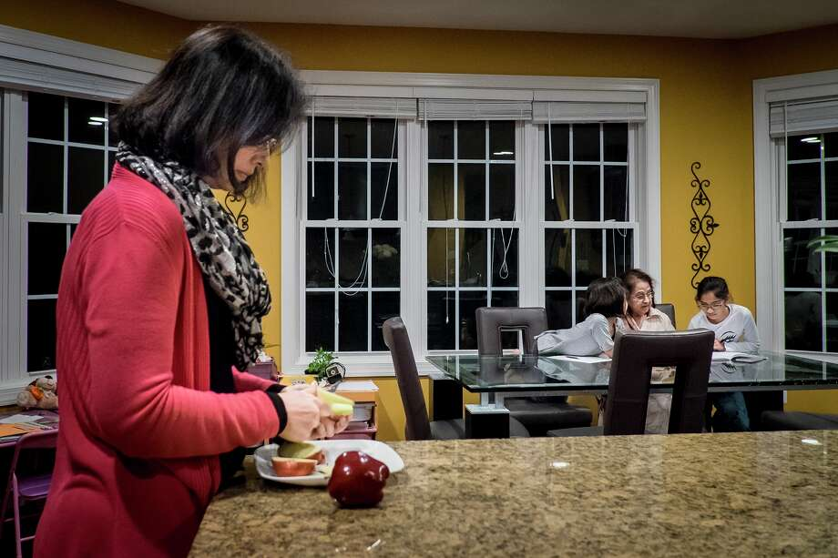 Samira Saddiqi fixes a snack. Her parents and her mother-in-law also live in her home, and her marriage and her husband's health have been strained. Photo: Pete Marovich /Washington Post