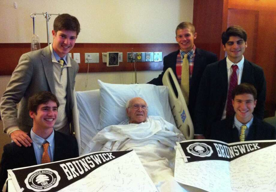Louis Zamperini, 94, a 1936 Berlin Olympic miler, World War II Army Air Corps bombardier, plane crash survivor and POW, was scheduled to speak recently during a special Brunswick School assembly, but for health reasons he was unable to appear. Instead, later that afternoon, five Brunswick high school students got to meet with Zamperini in his room at Greenwich Hospital. Front row, from left, Tommy Rosencranz (10th grade); Louis Zamperini; Jake Matthews (12th grade); back row, from left,  Willy Fein (11th grade); Michael Chronert (12th grade); Rick Salame (12th grade). Photo: Contributed Photo / Greenwich Time Contributed