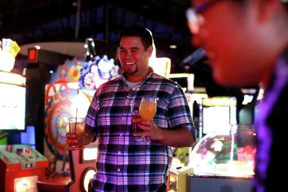 Tom Michaelson watches as Anney Han plays air hockey at Plank. Food and drink provide 80 percent of the Oakland spot's revenue, but the games keep the customers around longer.