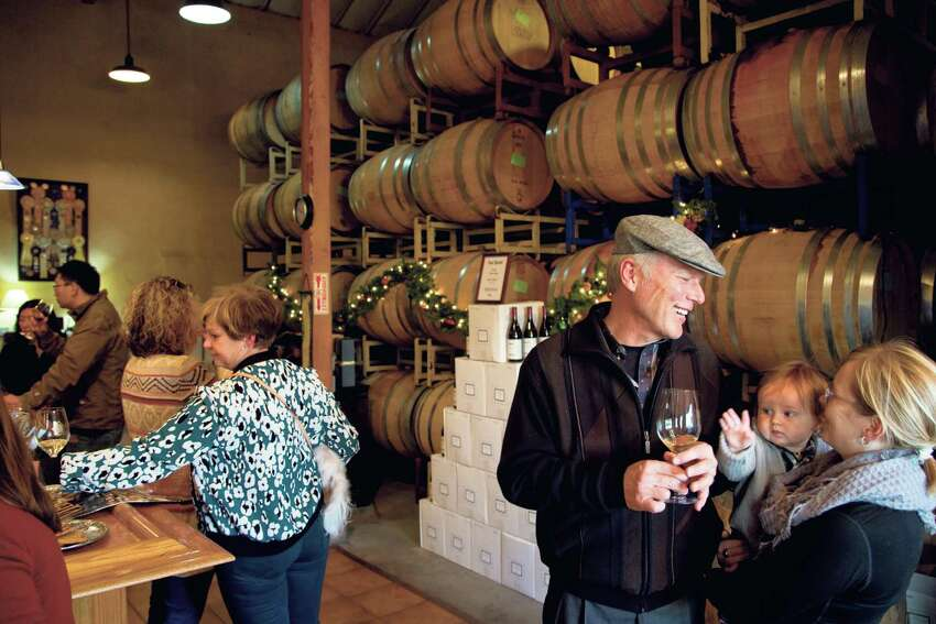 Steve Marshall talks to Morgen Marshall and her son Xander in the tasting room and barrel room at Claiborne & Churchill Vintners in San Luis Obispo., California December 20, 2014.