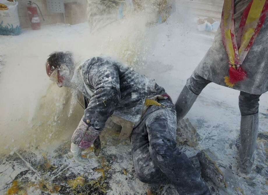 "Revelers, dressed in mock military uniforms, take part in the battle of ""Enfarinats"", a flour fight, in the town of Ibi, south-eastern Spain, on December 28, 2014. Ibi's citizens annually celebrate the Els Enfarinats, a 200-year-old traditional festival part of the celebrations of the Day of the Innocents, with a battle using flour, eggs and firecrackers outside the city town hall. Photo: JAIME REINA, AFP/Getty Images / AFP"
