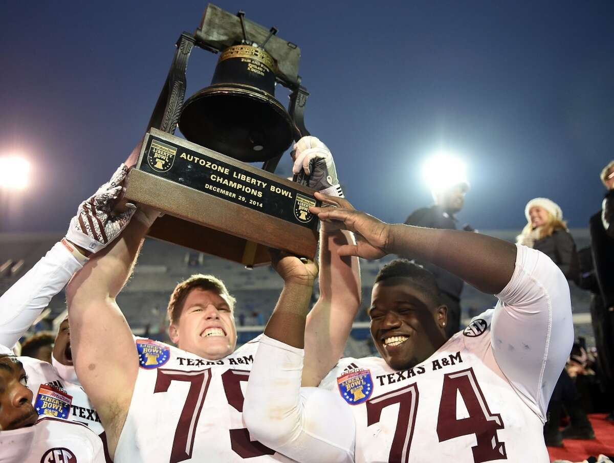 AutoZone Liberty Bowl (Dec. 29): Texas A&M 45, West Virginia 37 Record: 8-5 Germain Ifedi #74 and Joseph Cheek #79 of the Texas A&M Aggies hoist the trophy following a victory over the West Virginia Mountaineers in the 56th annual Autozone Liberty Bowl at Liberty Bowl Memorial Stadium on December 29, 2014 in Memphis, Tennessee. (Photo by Stacy Revere/Getty Images)