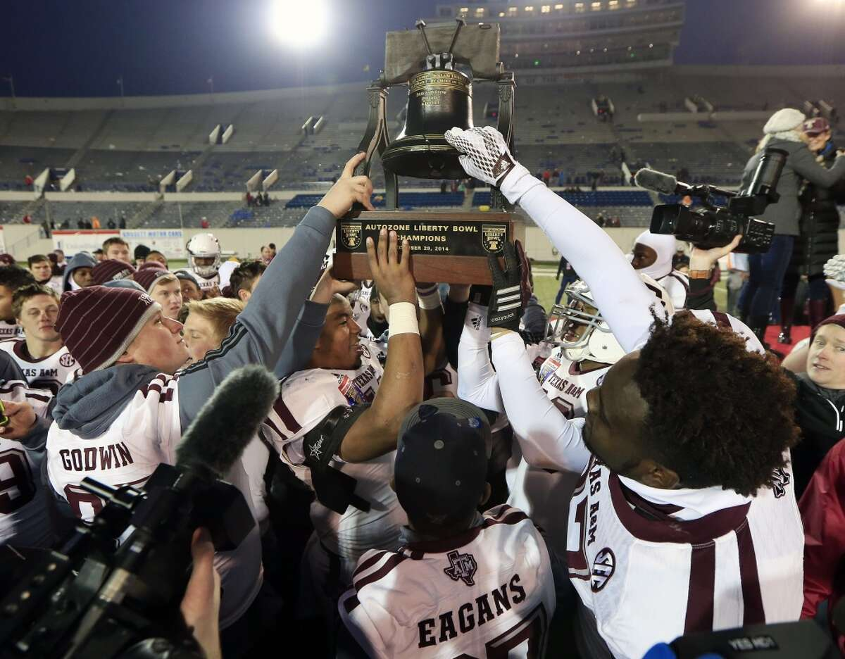 Texas A&M players celebrate with their trophy after defeating West Virginia in the Liberty Bowl NCAA college football game Monday, Dec. 29, 2014, in Memphis, Tenn. Texas A&M won 45-37. (AP Photo/Mark Humphrey)