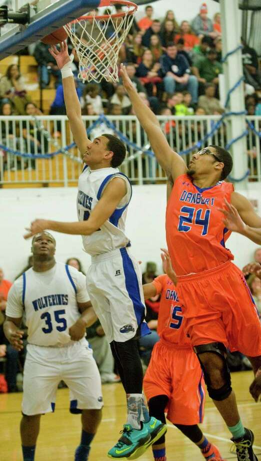 Abbott Tech High School's Yermy Zapata puts the ball up while Danbury High School's Marcus Fox defends in a game played at Abbott Tech. Monday, Dec. 29, 2014 Photo: Scott Mullin / The News-Times Freelance
