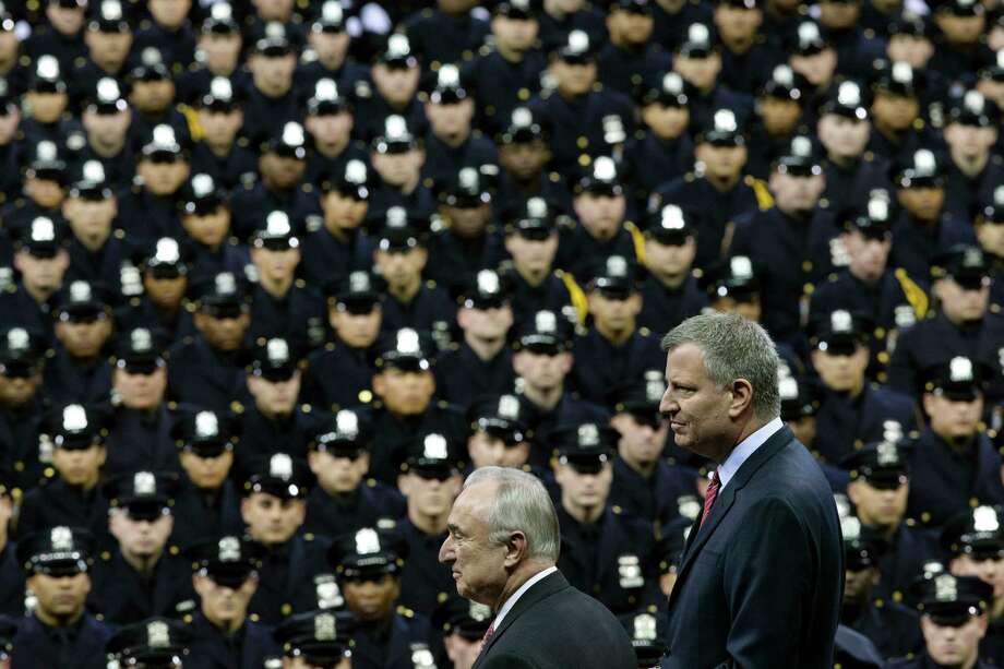 New York City Mayor Bill de Blasio, right, and NYPD police commissioner Bill Bratton, center, stand on stage during a New York Police Academy graduation ceremony, Monday, Dec. 29, 2014, at Madison Square Garden in New York. Nearly 1000 officers were sworn in as tensions between city hall and the NYPD continued following the Dec. 20 shooting deaths of officers Rafael Ramos and Wenjian Liu. (AP Photo/John Minchillo) ORG XMIT: NYJM118 Photo: John Minchillo / FR170537 AP