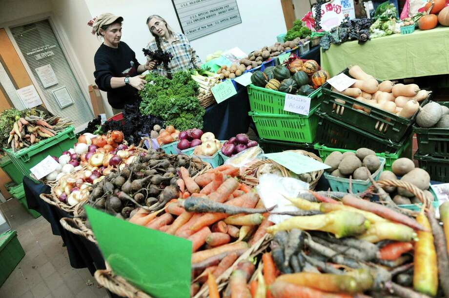 Sisters Jenn Ward, left, and Melissa Ward of Our Farm CSA have their produce for sale at the Troy Farmers Market on Saturday Dec. 20, 2014, at the Atrium in Troy, N.Y. (Cindy Schultz / Times Union) Photo: Cindy Schultz / 00029947A