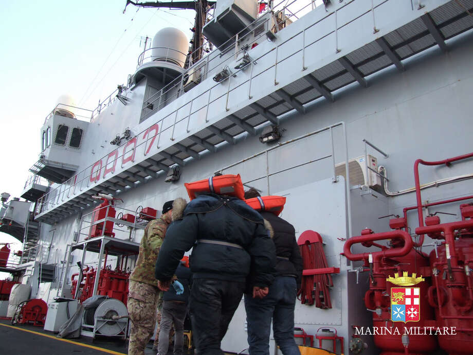 In this image released by the Italian Navy, passengers of the Italian-flagged Norman Atlantic, that caught fire in the Adriatic Sea, are rescued from the Italian Navy ship San Giorgio, Monday, Dec. 29, 2014. A cargo ship with 49 people evacuated from a Greek ferry that caught fire in the Adriatic Sea arrived in the Italian port of Bari on Monday, the first big group to reach land. More than 160 people remained trapped on the smoke-filled vessel adrift in frigid temperatures and rough seas between Italy and Albania. One person was killed in the risky rescue operation and two others were injured as Italian and Greek rescue ships and helicopters worked through the night plucking passengers off the stricken vessel and bringing them to safety aboard the 10 or so mercantile ships nearby that were summoned to help. (AP Photo/Italian Navy, ho) ORG XMIT: XAG108 / Italian Navy