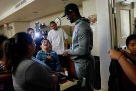Sergio Pimentel enjoys meeting Oakland Raiders' James Jones as the wide receiver brings Holiday cheer to Family Supportive Housing in San Jose, Calif., on Monday, December 22, 2014. Jones spent time at this homeless shelter as a youth.