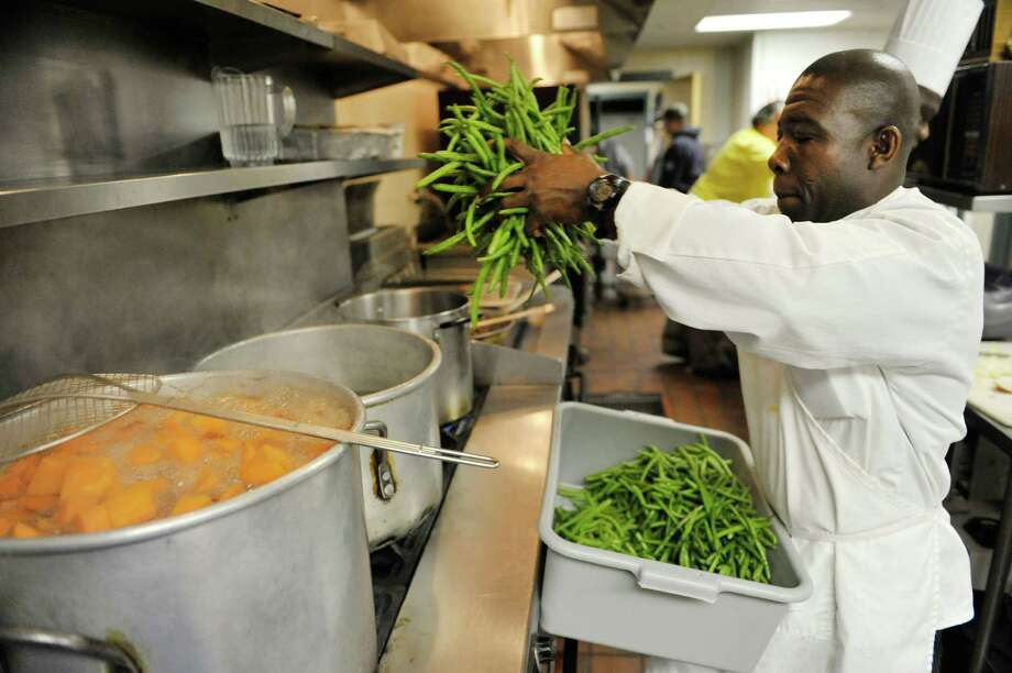 Kinnmo Ngoran, assistant chef, cooks string beans as staff and volunteers prepared lunch at Capital City Rescue Mission on Monday, Dec. 29, 2014, in Albany, N.Y.  Representatives from SEFCU traveled around the Capital Region on Monday to deliver checks totaling $132,500 to rescue missions and food pantries.  The Capital City Rescue Mission received $15,000.  This is the fifth year that SEFCU has given out checks to the organizations.  (Paul Buckowski / Times Union) Photo: Paul Buckowski / 00030017A
