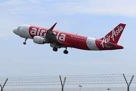 CORRECTS NUMBERS OF THE PASSENGERS -  In this May 9, 2014 photo, an AirAsia A320-200 plane takes off from Kuala Lumpur International Airport 2 in Sepang, Malaysia. An AirAsia plane with 162 people on board went missing on Sunday, Dec. 28, 2014 while flying over the Java Sea after taking off from Surabaya, Indonesia for Singapore. The plane in this photo is the same model but not the one which went missing in Indonesia Sunday.  (AP Photo/Joshua Paul)
