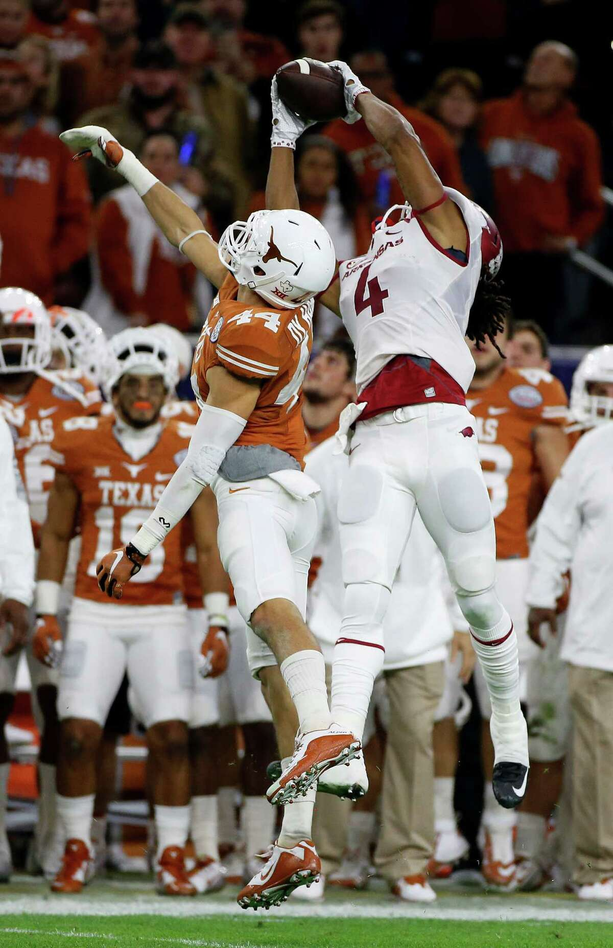 Arkansas wide receiver Keon Hatcher (4) catches a pass over Texas defensive back Dylan Haines (44) during the first quarter of the Texas Bowl at NRG Stadium on Dec. 29, 2014, in Houston.