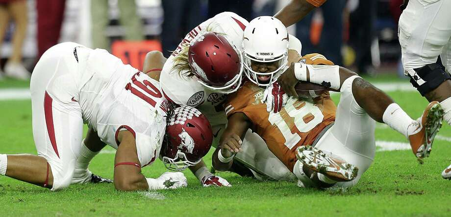 Texas quarterback Tyrone Swoopes (18) is brought down by Arkansas defensive lineman Mitchell Loewen (89) and defensive tackle Darius Philon (91) during the first quarter of the AdvoCare V100 Texas Bowl at NRG Stadium on Monday, Dec. 29, 2014, in Houston. ( Brett Coomer / Houston Chronicle ) Photo: Brett Coomer, Houston Chronicle / Houston Chronicle / © 2014 Houston Chronicle