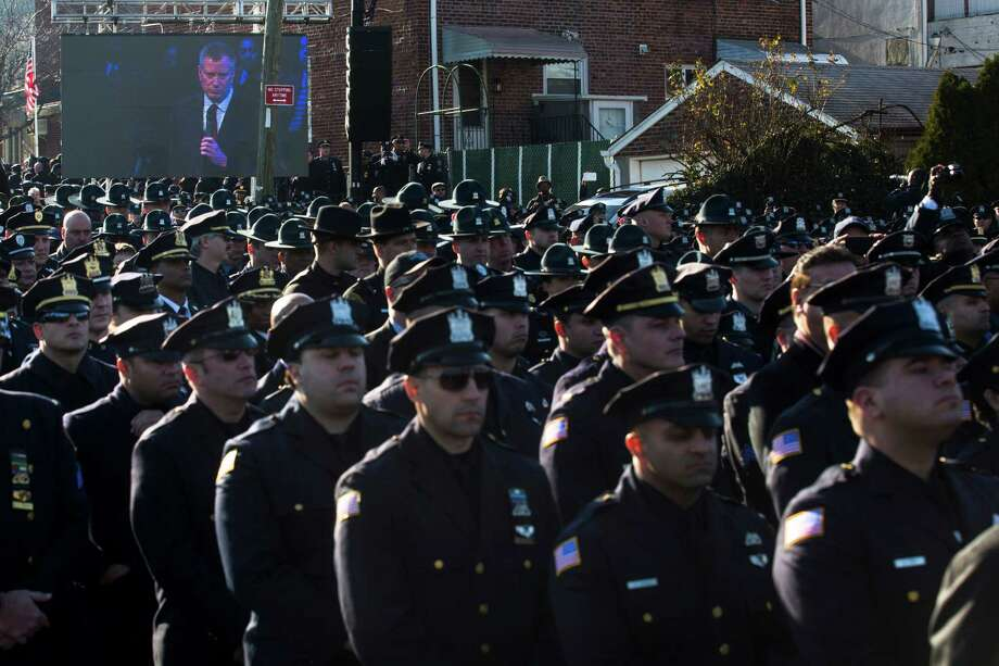 Police officers turn their backs as New York City Mayor Bill de Blasio speaks at the funeral of New York City police officer Rafael Ramos in the Glendale section of Queens, Saturday, Dec. 27, 2014, in New York. Ramos and his partner, officer Wenjian Liu, were killed Dec. 20 as they sat in their patrol car on a Brooklyn street. The shooter, Ismaaiyl Brinsley, later killed himself. (AP Photo/John Minchillo) ORG XMIT: NYJM116 Photo: John Minchillo, AP / FR170537 AP