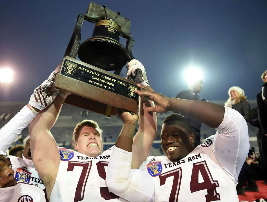 Germain Ifedi (right) and Joseph Cheek hoist the trophy following a victory over West Virginia in the 56th annual Autozone Liberty Bowl. The Aggies won 43-37. Photo: Stacy Revere /Getty Images / 2014 Getty Images