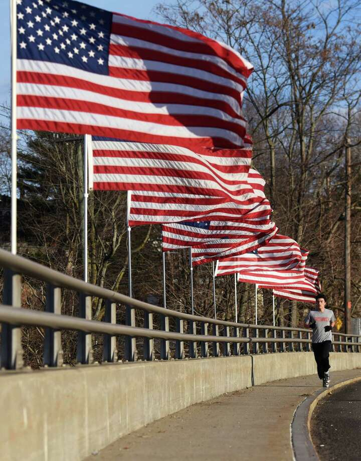 A runner passes by the row of American flags on the bridge spanning the Mianus River along Route 1 in the Cos Cob section of Greenwich, Conn. Monday, Dec. 29, 2014.  There is a movement afoot to rename that span of Post Road in honor of Greenwich Selectman David Theis, who died suddenly last week.  Theis was instrumental in starting the program by which American flags line the bridge.  The flags are not usually out at this time of year, but First Selectman Peter Tesei ordered them up in honor of Theis. Photo: Tyler Sizemore / Greenwich Time