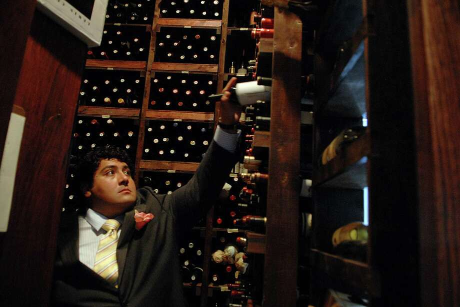 Dominick Purnomo, sommelier/owner of DP an American Brasserie in Albany, NY, checks stock in the wine room on Monday, July 13, 2009.  Restaurants and hotels in downtown Albany benefited from the Senate deadlock that took place over the last month.  (Paul Buckowski / Times Union) Photo: PAUL BUCKOWSKI / 00004715A
