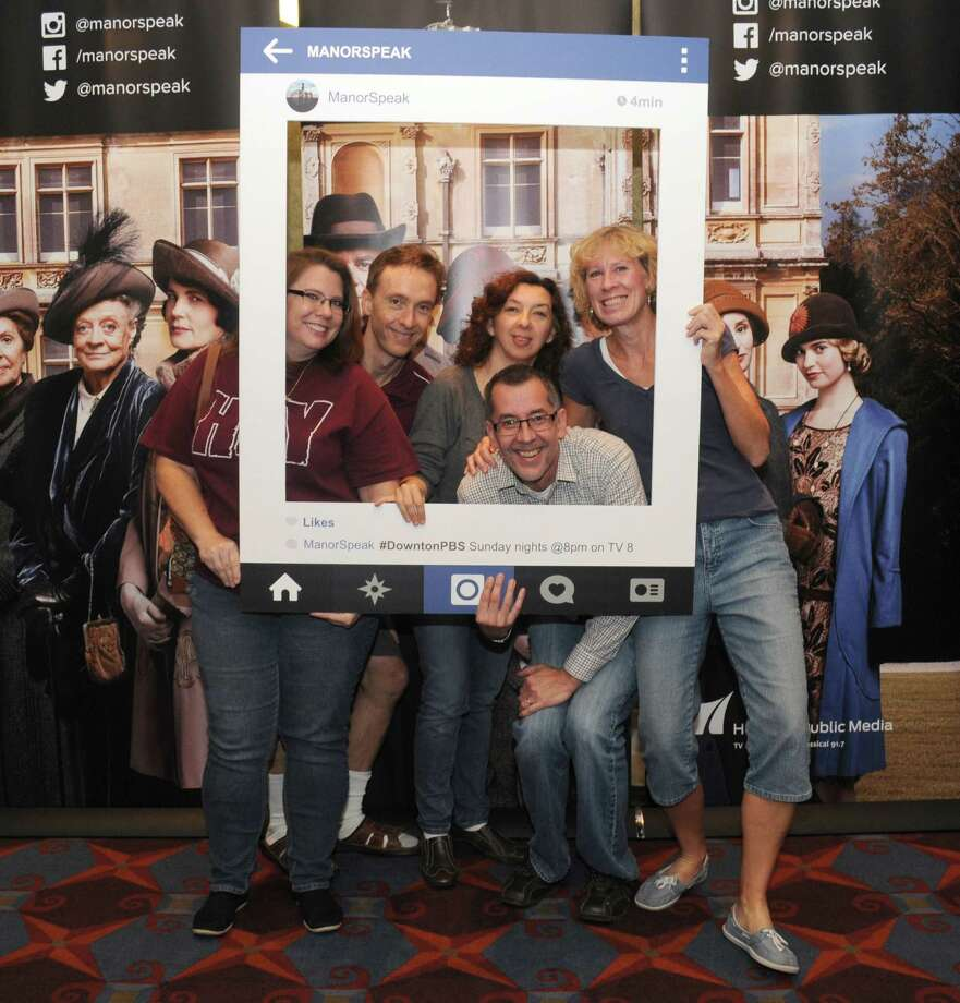 "Gayle Raines of Fresno, left, Jim Harris and Marisa Harris of Katy, and Corey Scheller and Joni Scheller of Sugar Land pose with a Instagram cut out in front of the ""Downton Abbey"" banner during the free screen of Season 5 premiere. Photo: George Wong / Freelance"