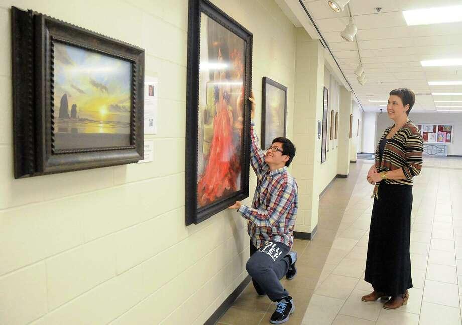 The Woodlands High School AP art student Zane Wang straightens a painting under the watchful eye of art instructor Jenny Lucas. Photo: David Hopper, Freelance / freelance