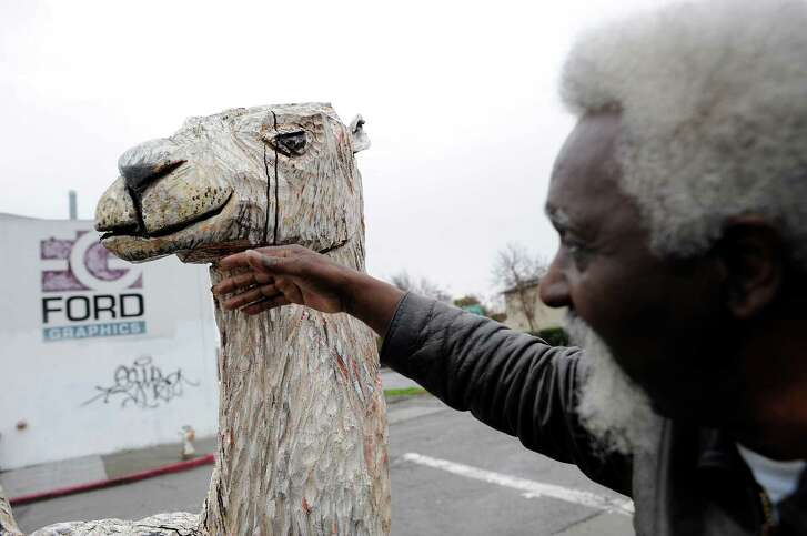 John Abduljaami looks over one of his large, hand-carved wood figures, a 6-foot-tall camel that is being stored at the Magnolia Yard, where he used to live, in West Oakland Dec.19.