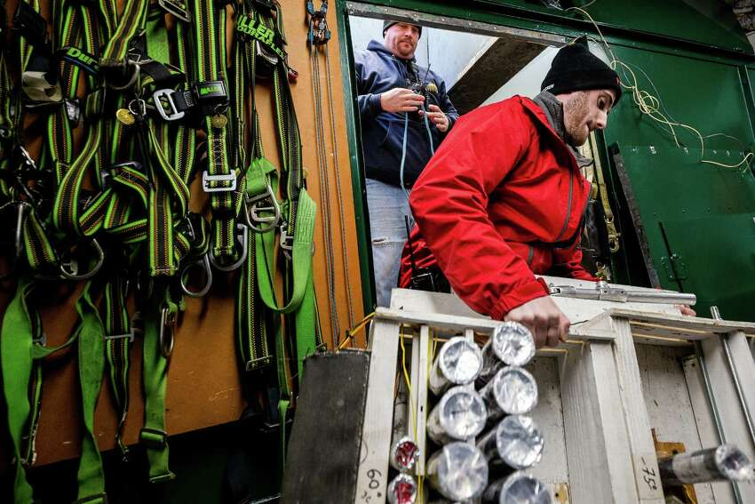 Crews from Pyro Spectaculars and the Space Needle work to install several thousand pyrotechnic shots for the upcoming, eight-minute T-Mobile New Year's fireworks display, photographed Tuesday, in Seattle.