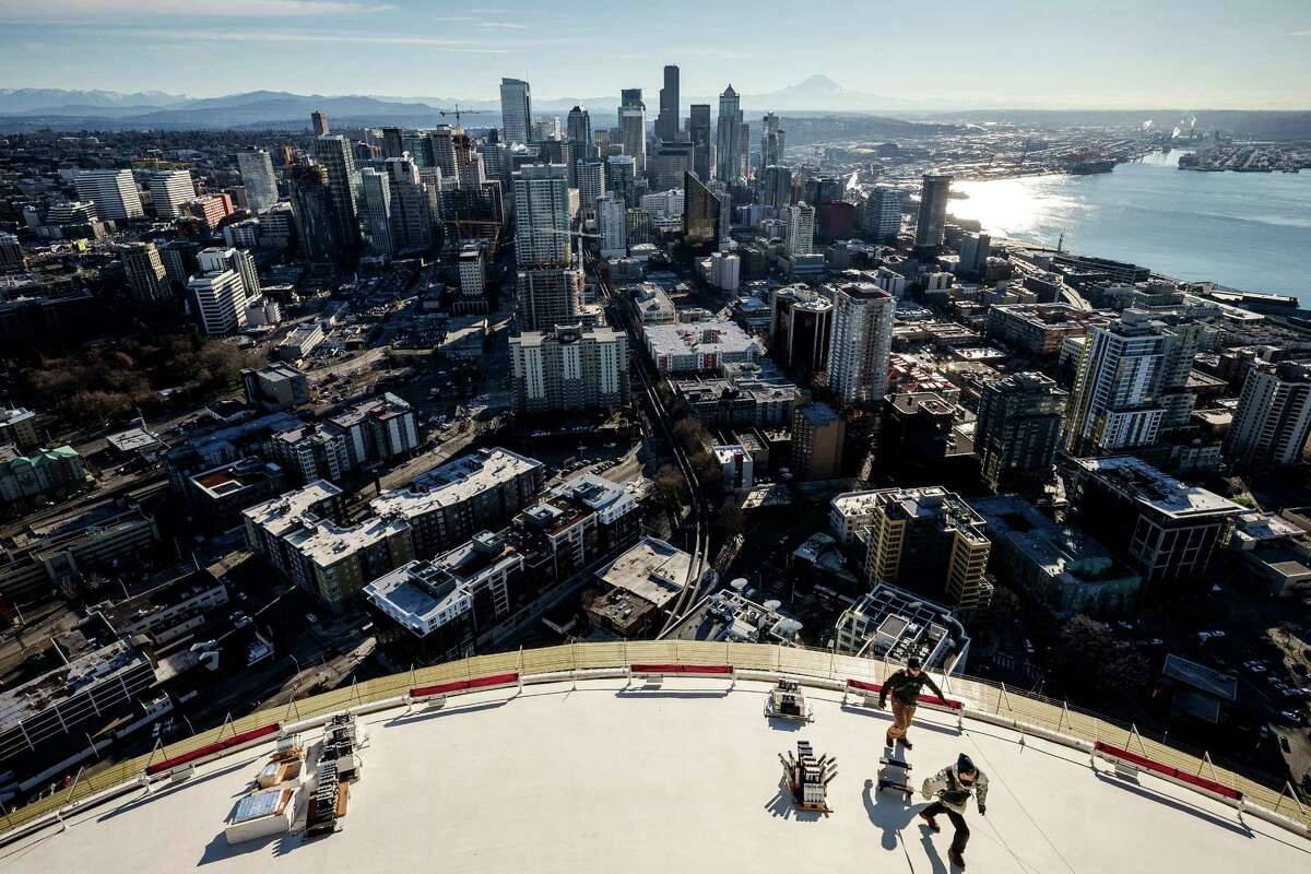 High above the city, crews from Pyro Spectaculars and the Space Needle work to install several thousand pyrotechnic shots for the upcoming, eight-minute T-Mobile New Year's fireworks display, photographed Tuesday, in Seattle.