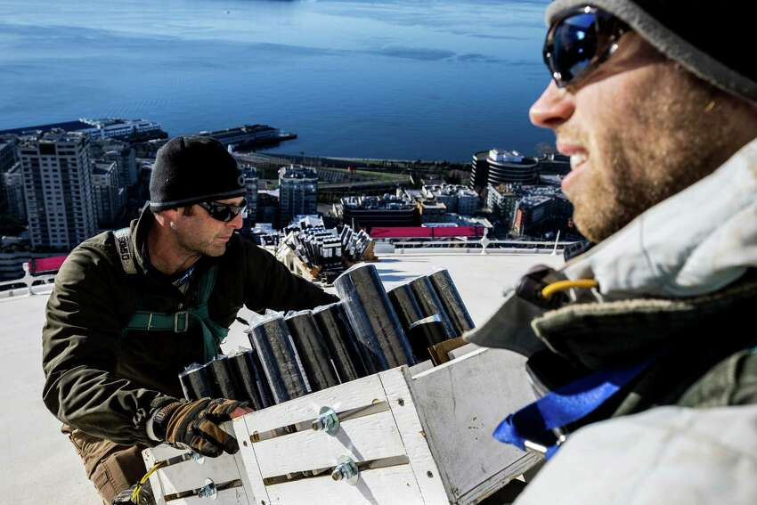 Scott Streeper, left, and Kevin Gilfillan, right, of Pyro Spectaculars work to install several thousand pyrotechnic shots on the roof of the Space Needle for the upcoming, eight-minute T-Mobile New Years at the Needle fireworks display, photographed Tuesday.