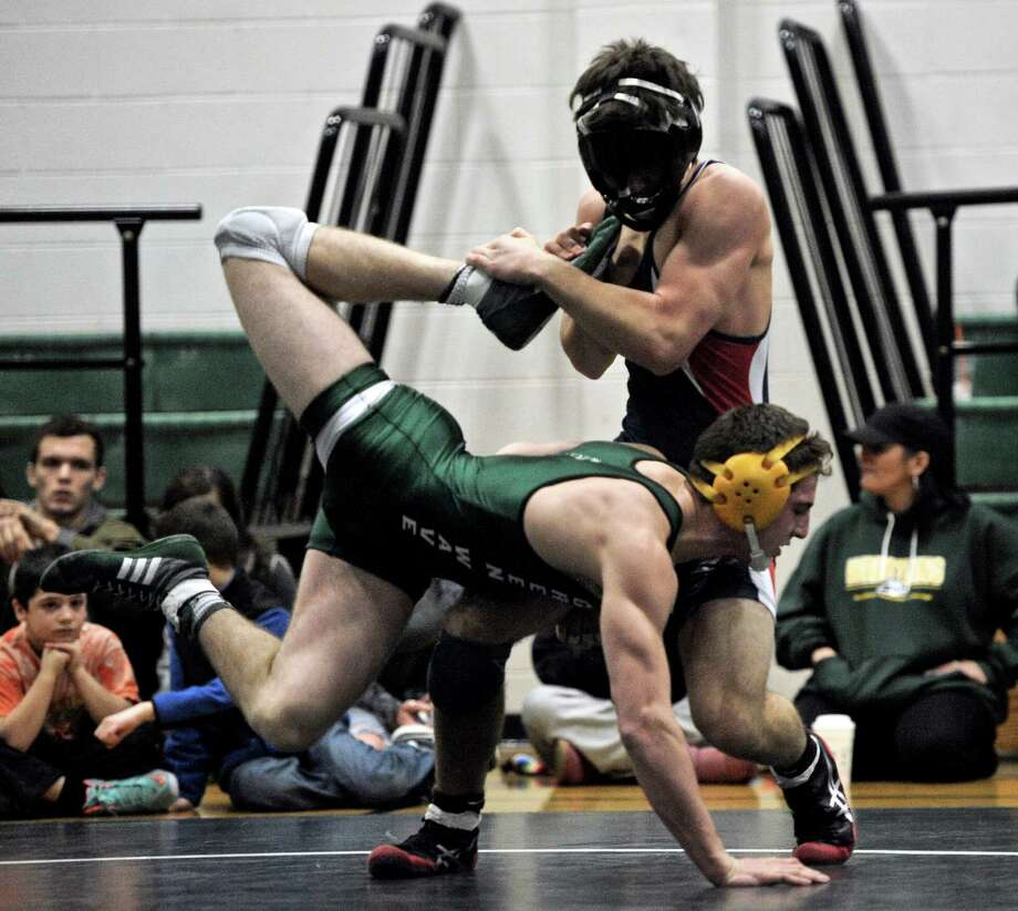 New Fairfield's Tyler Burlinson, top, and New Milford's Brett Leonard wrestle in the 152 pound weight class during a meet between New Fairfield and New Milford high schools, on Tuesday, December 30, 2014, in New Milford, Conn. New Milford won the meet 60-10. Burlinson is wearing a protective mask after breaking his nose in practice. Photo: H John Voorhees III / The News-Times