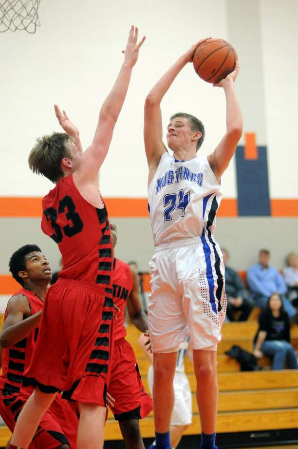 Friendswood junior forward Adam Hinchcliffe, right, shoots over a Fort Bend Austin defender during the 2013 Nike Classic in Katy. Photo: Jerry Baker, Freelance