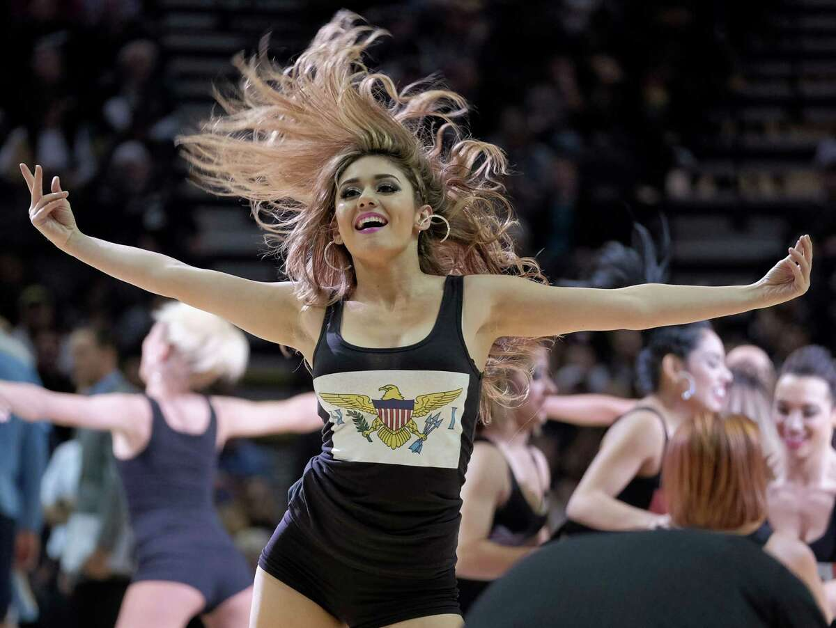 A San Antonio Spurs Silver Dancer performs during the second half of the Spurs' NBA basketball game against the Memphis Grizzlies, Wednesday, Dec. 17, 2014, in San Antonio. Memphis won 117-116 in triple overtime. (AP Photo/Darren Abate)