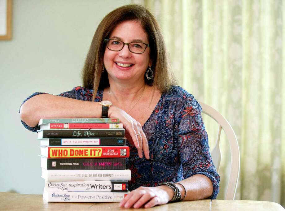 Sarah Darer Littman poses for a photo in her Cos Cob home on Tuesday, December 30, 2014, with a stack of books she authored. Littman is one of the authors and artists who volunteered to write a myster called The Great Connecticut Caper for CT Center for the Book. Littman authored chapter 3 of the children's e-book. Photo: Lindsay Perry / Stamford Advocate