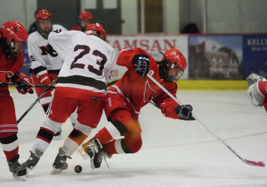 New Canaan's Lauren Williams, center, checks Greenwich's Jennie Piotrozki near the goal during New Canaan's 6-2 win over Greenwich in the FCIAC high school girls hockey game at the Darien Ice Rink in Darien, Conn. Tuesday, Dec. 30, 2014. Photo: Tyler Sizemore / Greenwich Time