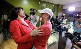 Alison Holcomb, left, of the Washington state ACLU, shares a laugh with first customer Deb Greene at Seattle's Cannabis City in July.