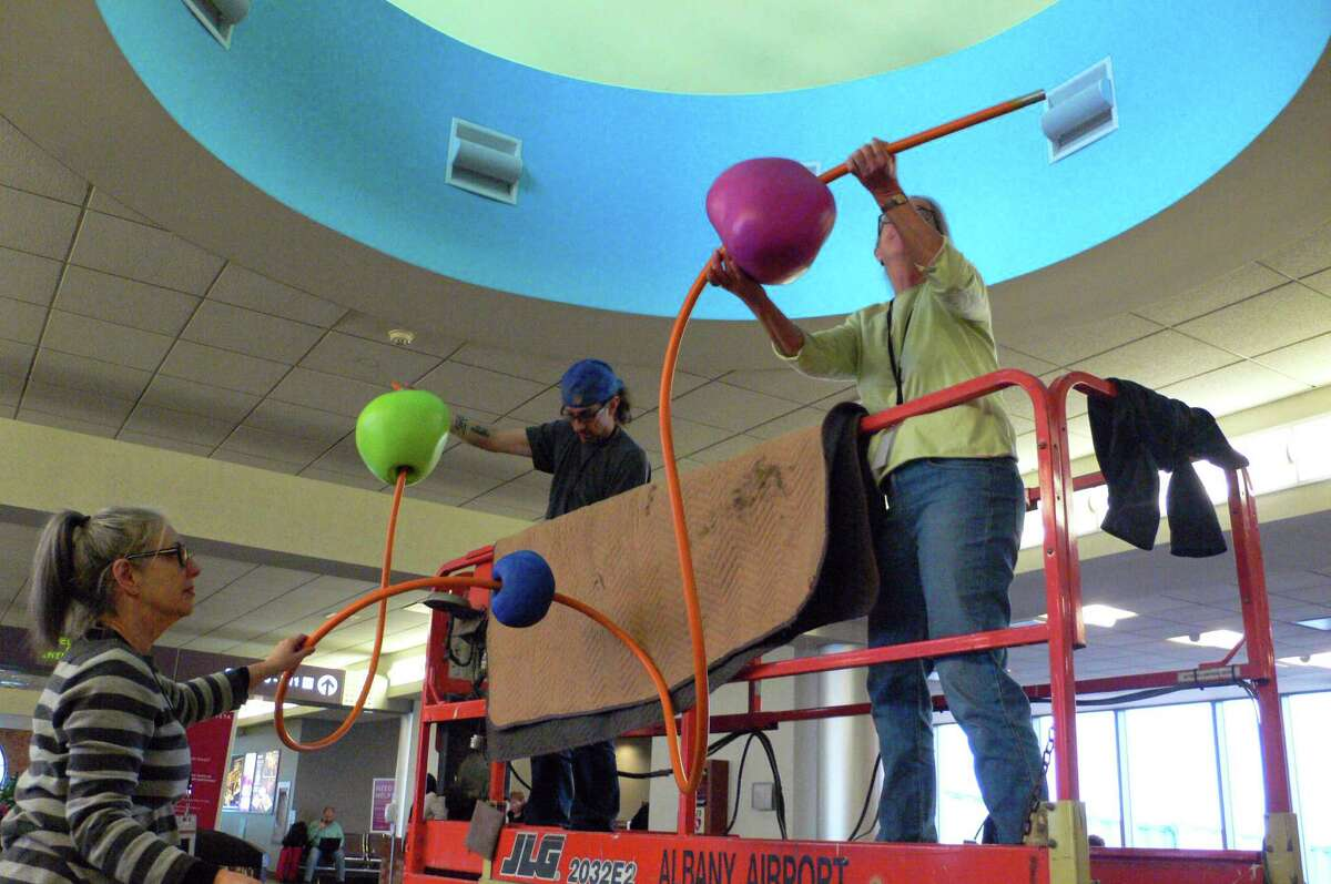 """L to R: Sharon Bates, Nick Warne and Roberley Bell installing """"Chasing the Sky."""" Photo by Amy Griffin."""