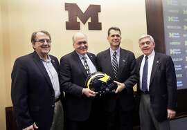 From left, former Michigan coach Lloyd Carr, interim athletic director Jim Hackett, new head coach Jim Harbaugh and former coach Gary Moeller Jim Harbaugh, pose for a photo after Harbaugh was introduced during an NCAA college football news conference Tuesday, Dec. 30, 2014, in Ann Arbor, Mich. (AP Photo/Carlos Osorio)