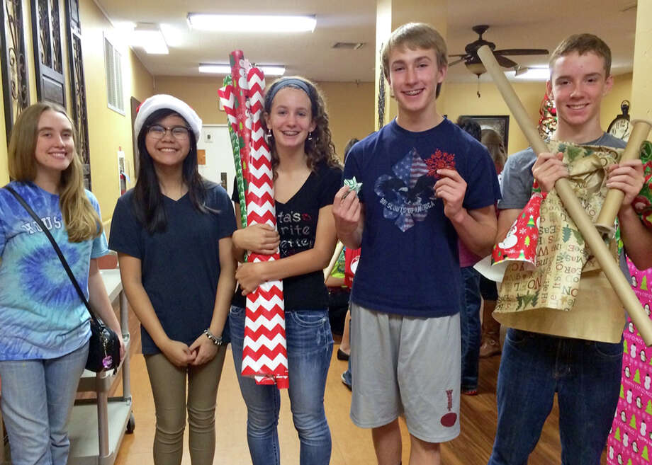 Pearland High Schoolís Leah Phillips, left, and GT Academy students Ashley Dinh, Abigail Smaistrla, Jacob Phillips and Nicholas Johnson prepare to decorate doors at Windsong Village assisted-living facility. Photo: PISD